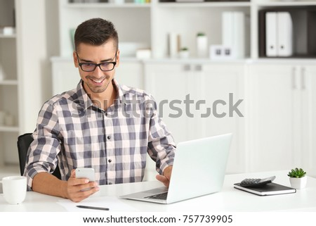 Attractive man with laptop and smartphone in office #757739905