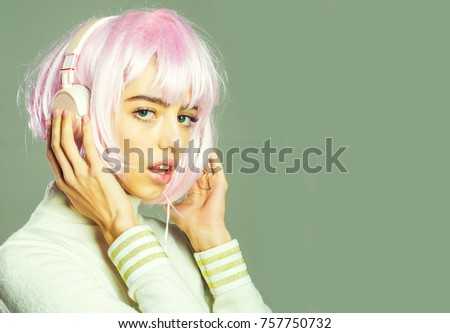 young pretty woman or cute sexy girl with pink glamour hair wig in fashionable shirt, poses on grey background with music headset, copy space #757750732