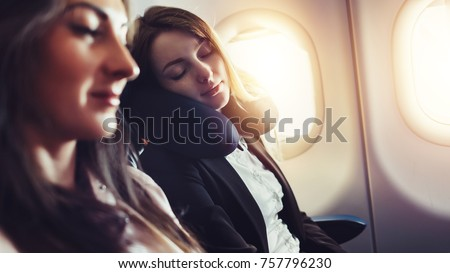 Girlfriends traveling by plane. A female passenger sleeping on neck cushion in airplane. #757796230
