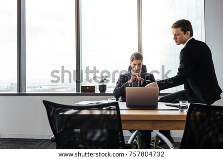 Two young corporate professionals working together at office desk. Business people discussing work in office and looking at laptop. #757804732