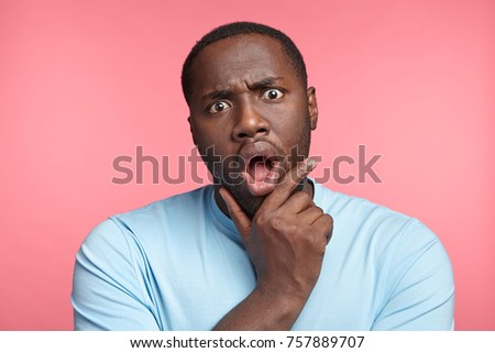 Curious dark skinned Afro American guy stares at camera with widely opened mouth, listens to scientific lecture in great interest, surprised with new discovery, can`t believe about unknown facts #757889707