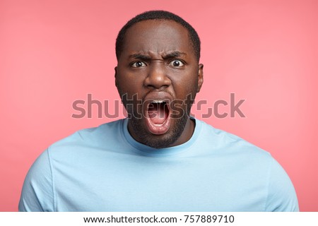 Furious dark skinned male screams loudly, annoyed with interlocutor, expresses negative emotions and feelings, keeps mouth widely opened. Angry African boss shouts at coworkers, being strict #757889710