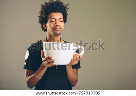 young happy african man holding a funny huge and oversized cup of black coffee in caffeine addiction concept #757919305