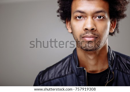 Positive guy with African hairstyle and dark skinlooking cheerfully into camera. Young dark-skinned male with smile dressed elegantly #757919308