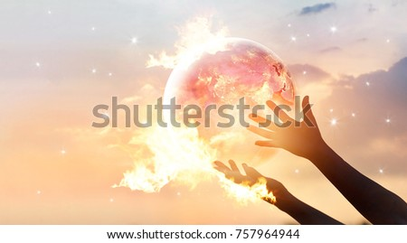 Save the world energy campaign. Planet earth with flame on human hands show energy consumption of humanity at night, Elements of this image furnished by NASA  #757964944