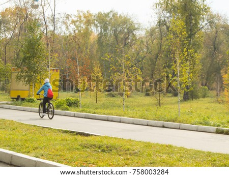 A girl rides a Bicycle in a city Park in autumn. #758003284