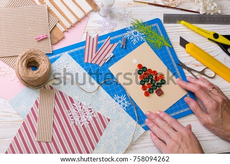 scrapbook background. Girl make christmas postcard from buttons and tools with decoration  #758094262
