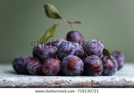 Plum. Fresh plum. Harvest. Autumn harvest. Autumn. Blue plums. Fresh plums on a wooden surface. Fresh plums on wooden table background. Слива. Урожай. #758130721