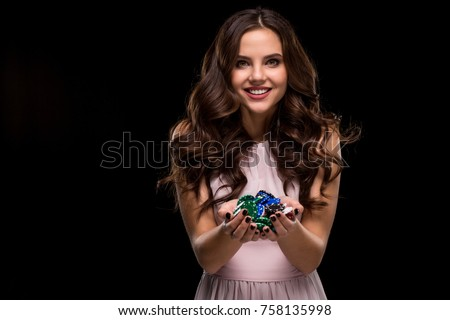 Female Poker player with paint black nails hold her poker chips to make a bet. Gambling and casino business concept