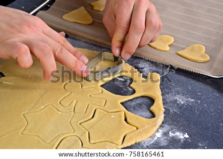 Men's hands baking Christmas gingerbread cookies on a table #758165461