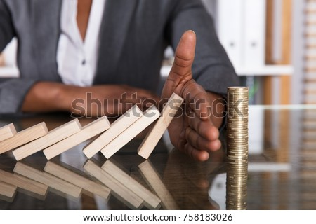Close-up Of A Human Hand Stopping Wooden Blocks From Falling On Stacked Coins Over Desk Royalty-Free Stock Photo #758183026