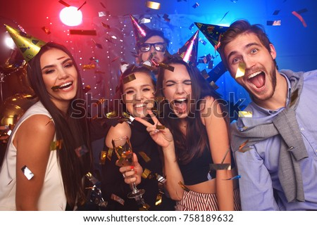 Friends making big party in the night. Four people throwing confetti and drinking champagne Royalty-Free Stock Photo #758189632