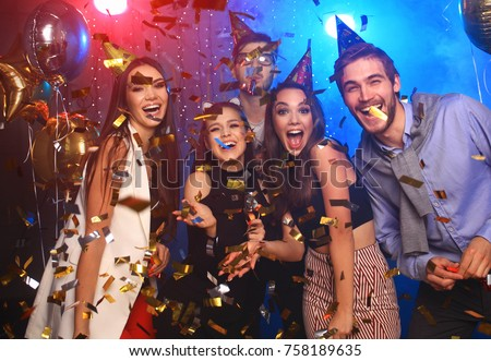 Friends making big party in the night. Four people throwing confetti and drinking champagne Royalty-Free Stock Photo #758189635