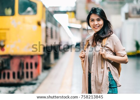 Happy beautiful traveler Asian woman with backpack at train station ready to start her journey. #758213845