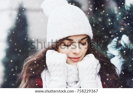 Outdoor close up portrait of young beautiful happy smiling girl wearing white knitted beanie hat, scarf and gloves. Model posing in street. Winter holidays concept. Toned #758229367