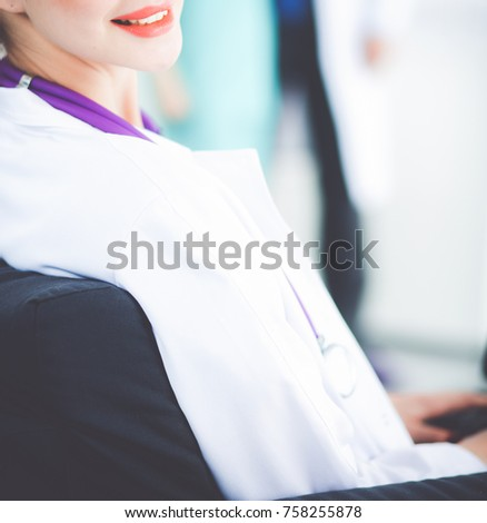 Beautiful young smiling female doctor sitting at the desk #758255878