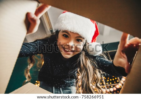 Surprised cute child girl opening a Christmas present. Little kid having fun near decorated tree indoors.  Happy  holidays and New Year.