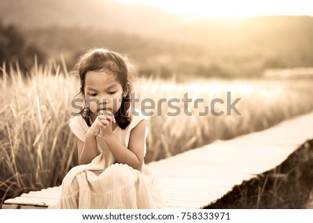 Lonely and sad little girl sitting on bamboo walkway in the paddy field in vintage color tone #758333971