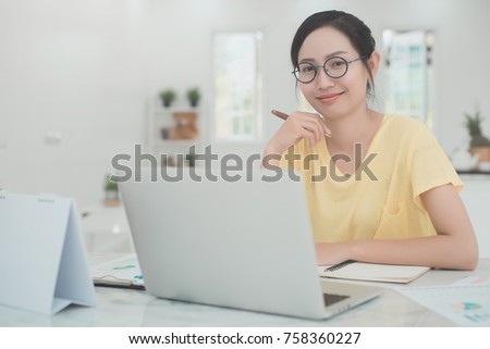 Asian woman working on laptop at home office. Close up portrait girl with computer laptop on table. #758360227