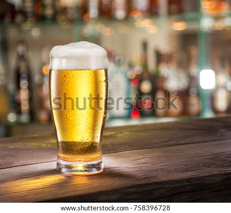 Frosty glass of light beer on the bar counter. #758396728