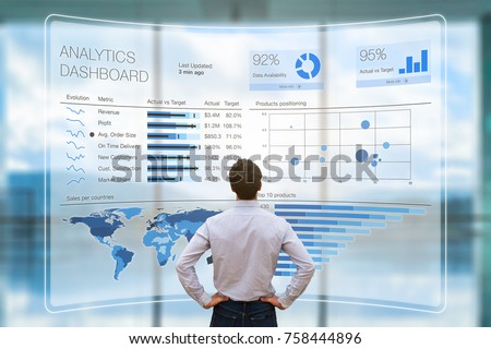 Businessman analyzing a business analytics (BA) or intelligence (BI) dashboard on virtual screen showing sales and operations data statistics charts and key performance indicators (KPI) Royalty-Free Stock Photo #758444896