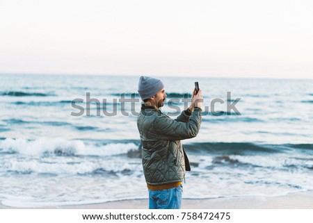 Young beautiful man using smart phone at the beach during sunset light. Modern guy taking picture with mobile phone. Sunset light on the beach background