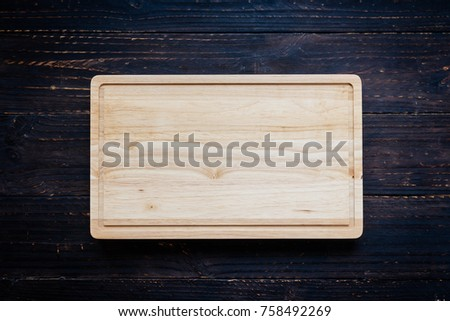 Wood cutting board on wooden background with copy space #758492269