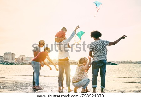 Happy familes flying with kite and having fun on the beach - Parents playing with children outdoor - Travel,love and holidays concept - Main focus on right woman - Warm filter #758521870