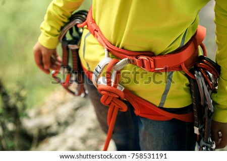 rock climber standing with climbing gears and rope   #758531191