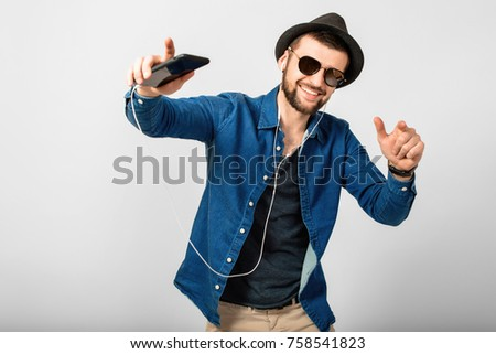 young handsome man on white studio background, isolated, listening to music on earphones, holding phone, smiling, happy #758541823