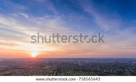 Aerial view of dramatic sunset or sunrise and blue sky over city. #758565643