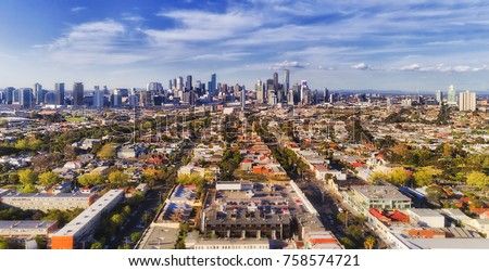 Aerial view of Melbourne city CBD high-rise towers from Port Melbourne and Southbank above residential suburb house roofs and local streets, roads, cars and parks. Royalty-Free Stock Photo #758574721