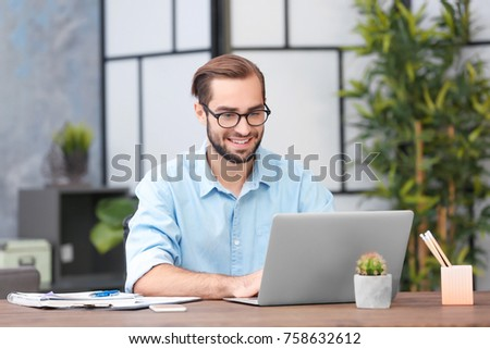 Young man using laptop in office #758632612