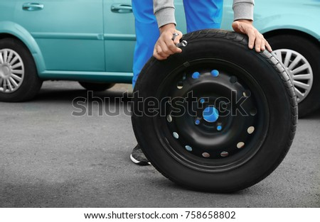 Young male mechanic changing wheel at service station #758658802