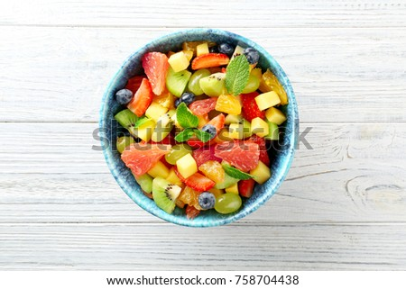 Bowl of fresh fruit salad on wooden table #758704438