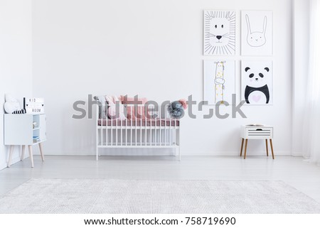 Four pictures on wall above cabinet in bright girl's room with pastel pink pillows on bed