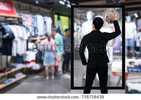 Augmented reality marketing technology concept. Businessman using smart glass digital signage , AR application to select and buy items in retail fashion shop.