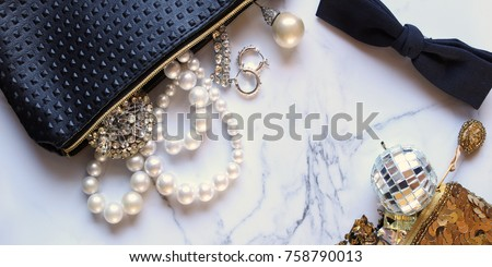 Luxury jewelry and bags spilling with items onto white marble copy space. #758790013