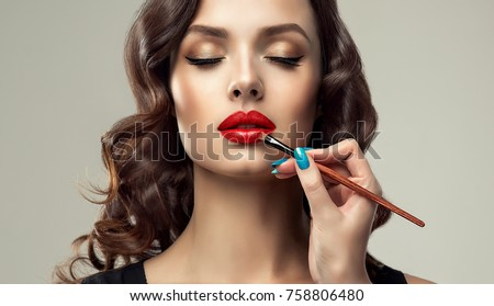 Makeup artist applies  red lipstick  . Beautiful woman face. Hand of make-up master, painting lips of young beauty  model girl . Make up in process  Royalty-Free Stock Photo #758806480