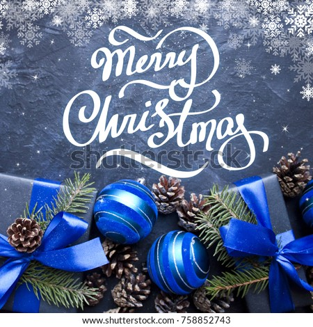Merry Christmas hand lettering. Christmas gift with blue ribbon and blue balls, tree branches and cones on dark blue background. Royalty-Free Stock Photo #758852743