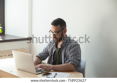 Millennial businessman sitting and typing on laptop in home office. Confident manager wearing glasses analyzing data on computer #758923627