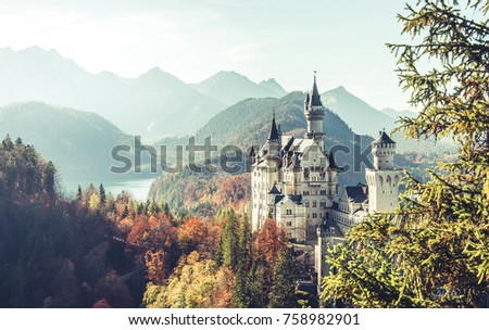 Neuschwanstein Castle under Sunlight with Mountain Hills on Background, Amazing Landscape Scenery. Picture of the fairy tale Castle near Munich in Bavaria, Germany. Vintage Style. Instagram Filter.