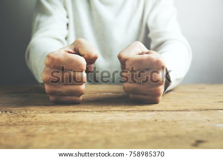 man fists clenched on a wooden table in anger Royalty-Free Stock Photo #758985370