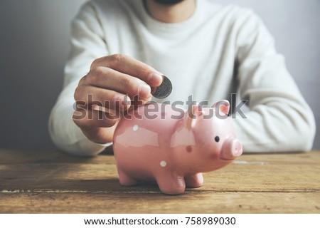 Man putting coin in piggy bank. Saving money concept #758989030