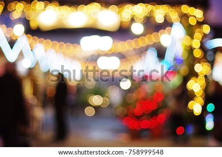 Colorful bokeh  defocused Christmas fairy lights. Silhouette of  walking man in the lights of a Christmas market, New Year's fair