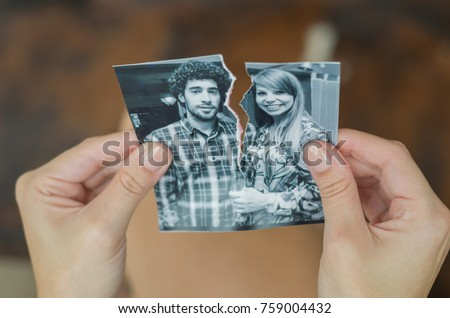 Great concept of divorce, betrayal, separation, woman hand ripping photo of the couple.