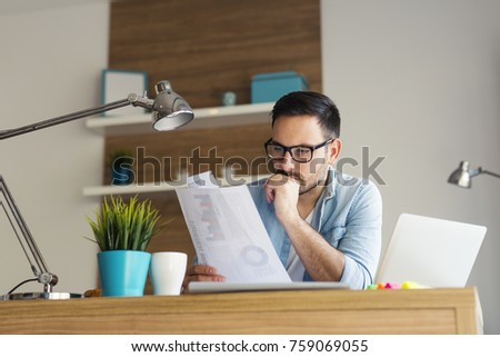 Young serious freelancer analyzing statistical data at his home #759069055