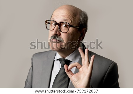 corporate close up portrait bald 60s happy and confident business posing neat and tidy smiling in okay and all right hand finger sign isolated on grey background in work and career success concept