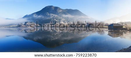 tranquil winter scenery at lake shore schliersee, upper bavaria, with mountain reflecting in the water #759223870