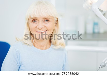 Caring about teeth. Close up of cheerful woman expressing satisfaction while sitting on dental chair and smiling at you #759256042